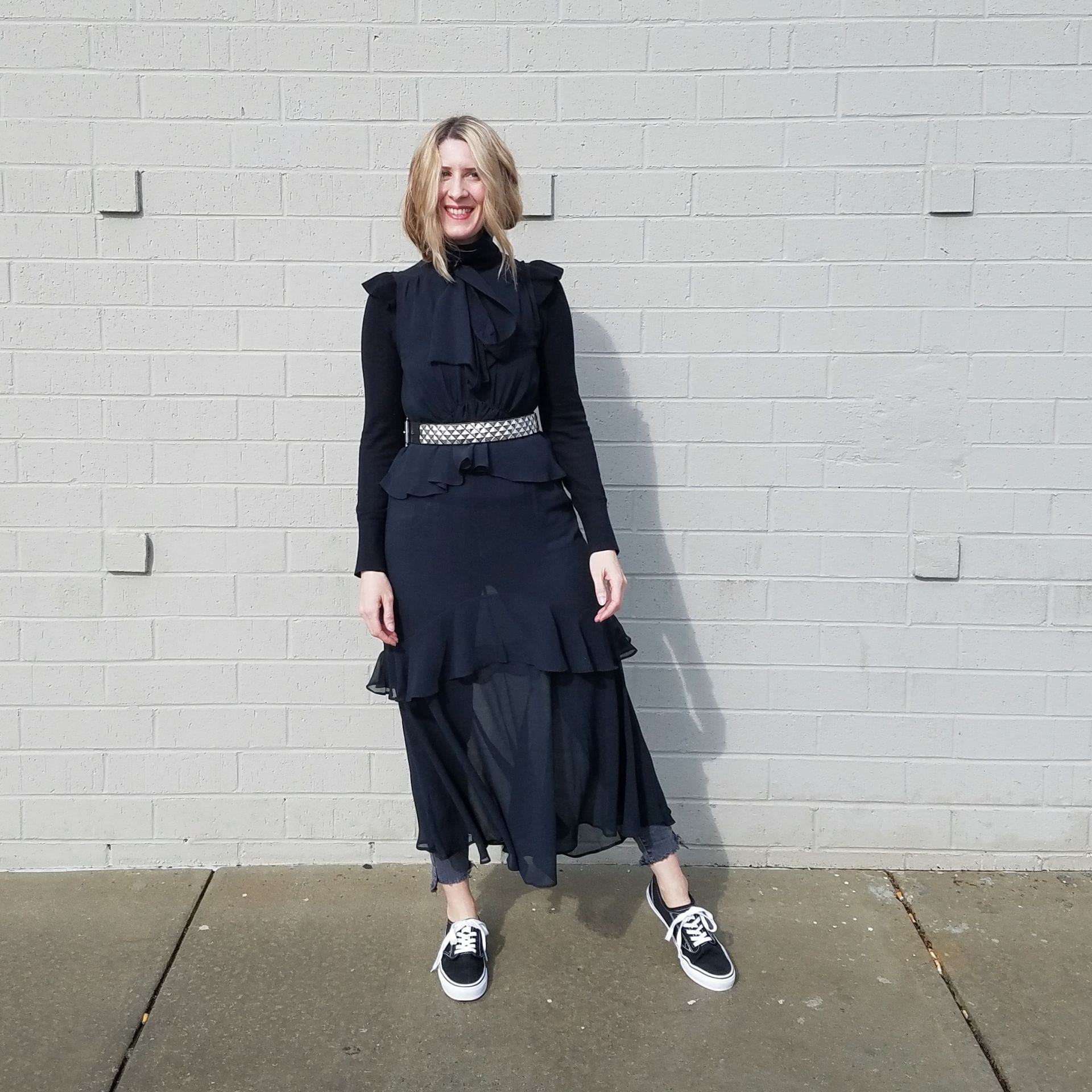 A sheer black dress layered over jans and belted around the waist with a studded belt